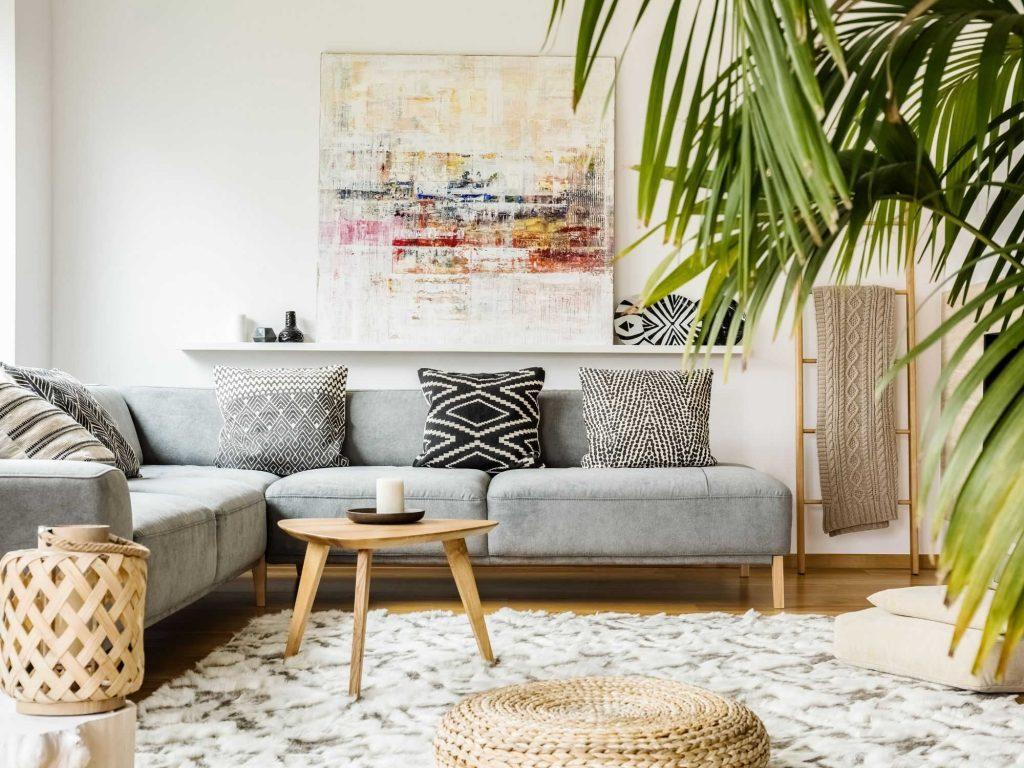 living room with grey sofa, cream rug and plants