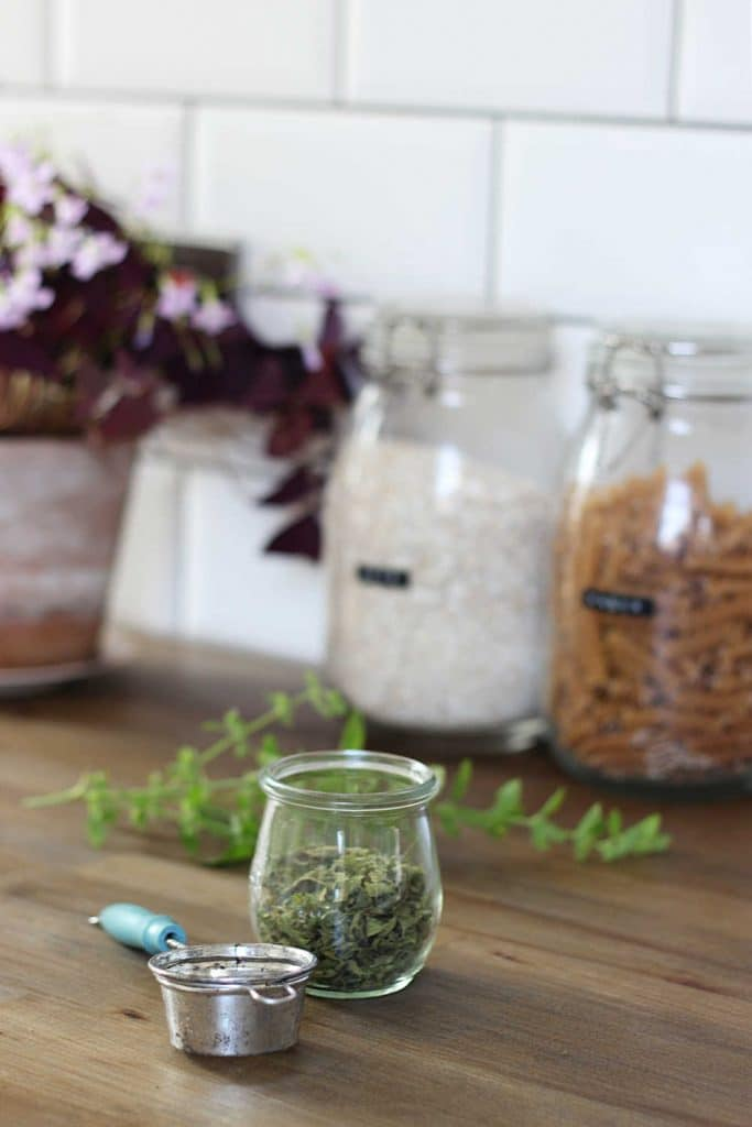 A jar containing dried lemon balm leaves next to a tea strainer