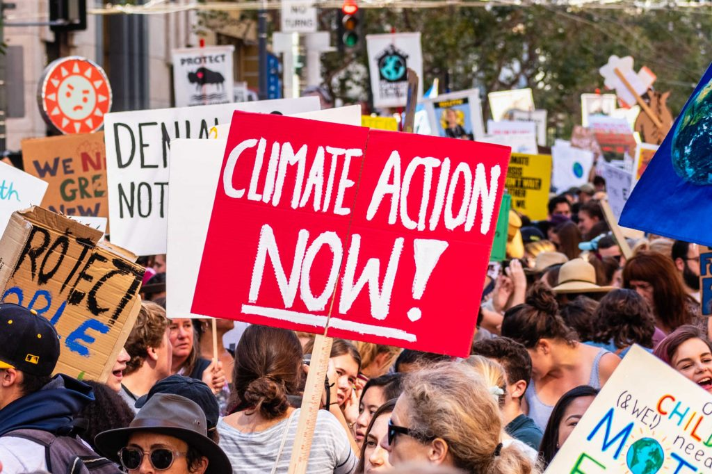 """crowd shot of climate change protest, with red banner in centre that says """"climate action now"""" in response to Cambo Oil Field"""