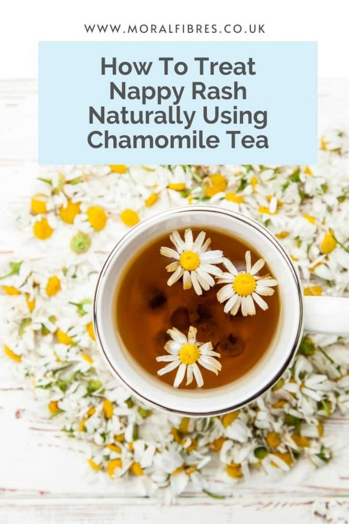 """A cup of chamomile tea, on a white surface surrounded by chamomile flowers with a blue text box that says """"how to treat nappy rash naturally using chamomile tea""""."""