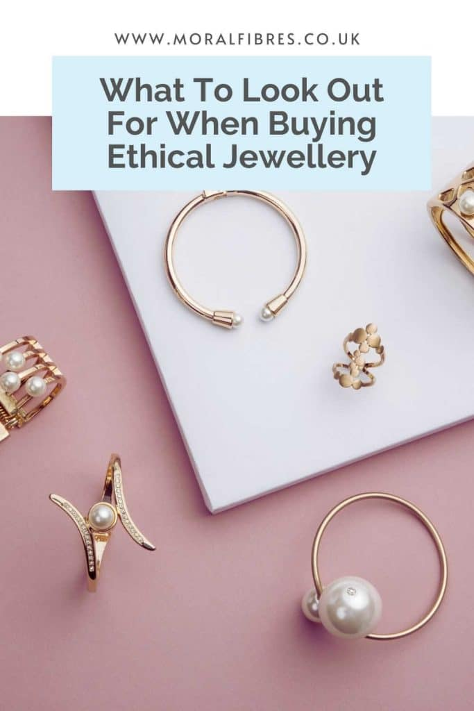 Flat lay of gold jewellery or jewelry on a pink background with a blue text box that says what to look out for when buying ethical jewellery