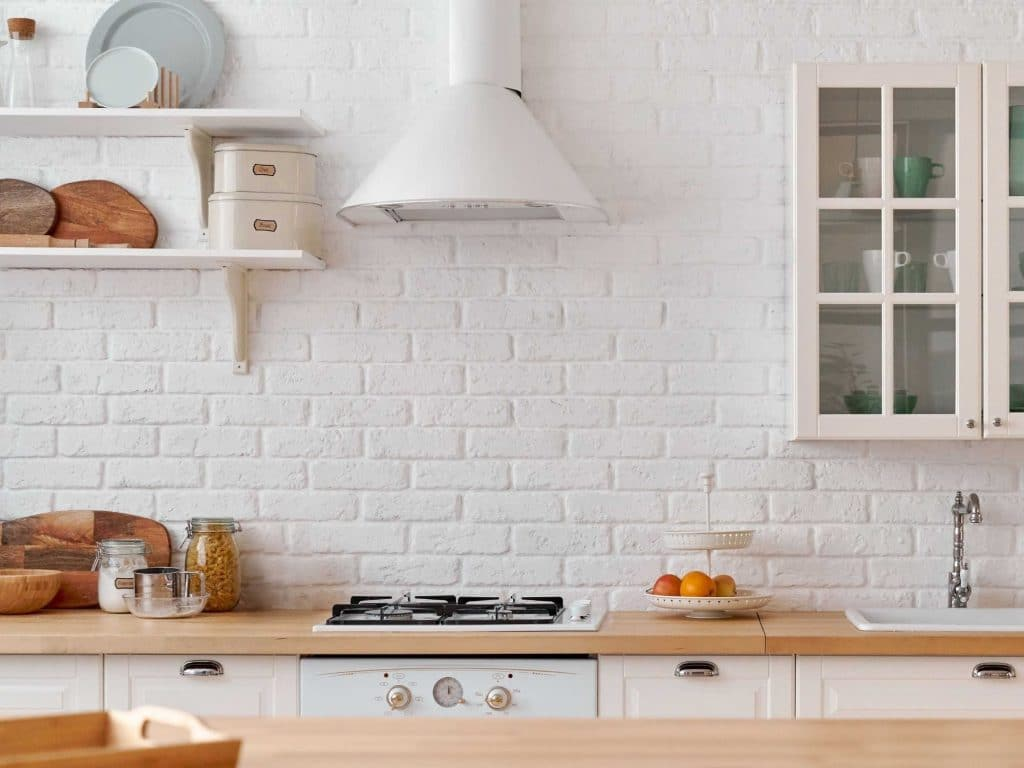 Cream kitchen with wooden worktops and white exposed brick walls
