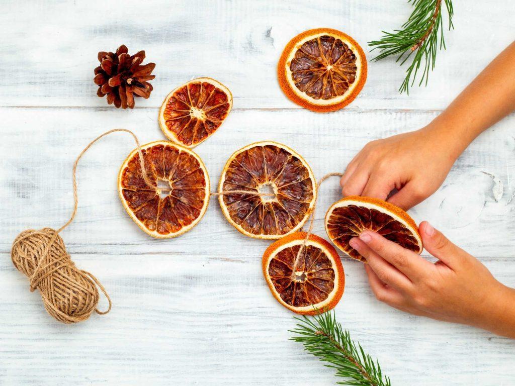 person threading a dried orange slice garland